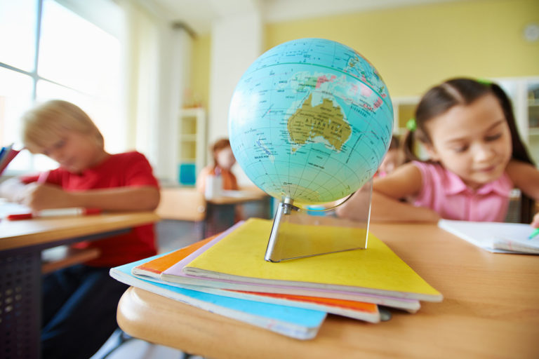 globe on desk with school children